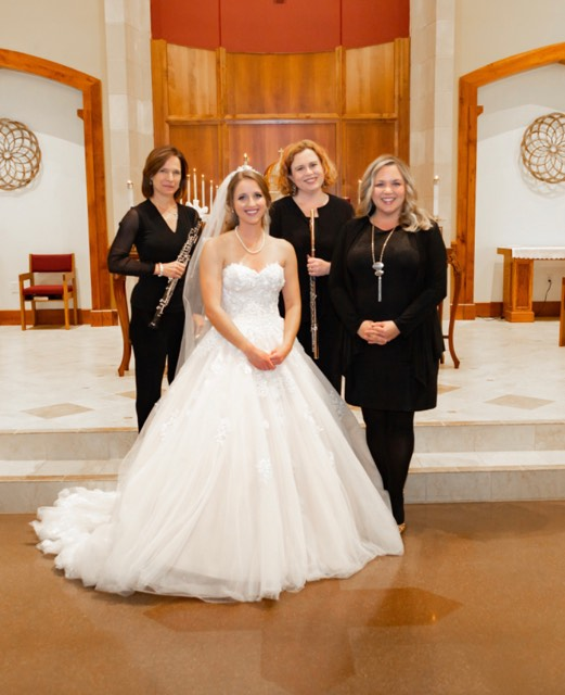 The trio standing with a bride in a church.